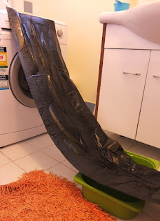 Image: Plastic bag slide attached to washing machine in bathroom with tray for catching liquid at bottom