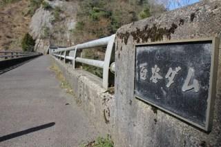 左岸よりダム湖側の天端高欄に取り付けられたダム銘板を望む