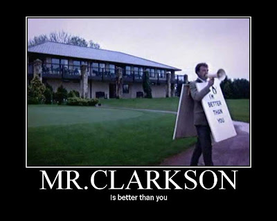 Jeremy Clarkson is on the lawn outside a large house, wearing a sandwich-board and bellowing into a megaphone.  The sandwich-board reads *I'm Better Than You