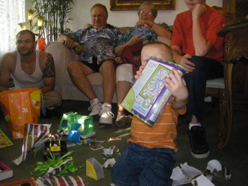 More presents with Nana, Papa, and Uncle Tim in the background.