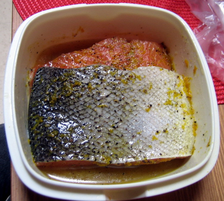 The two salmon fillets on top of each other in a fish sandwich. Make sure to flip over the sandwich every 12 hours so the rub penetrates the fish evenly