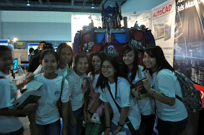 First year students pose behind a huge transformer robot.