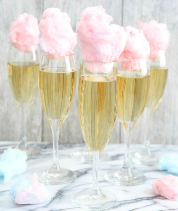 Unicorn party ideas, five glasses of champagne topped with pink cotton candy
