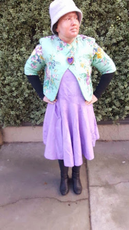 Carly findlay wearing purple dress, Aqua quilted jacket, purple hat, black boots
