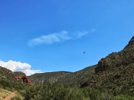 Hiking to Wet Beaver Creek (3 mi) in the Coconino National Forest when we saw Fire Dept. truck and ambulance in the parking lot and this helicopter flying in. It circled a few times and hovered before continuing behind us and landed.