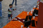 Mexican boy, standing on a cobblestone street of San Miguel de Allende, Mexico is  pointing at a Day of the Dead (Dia de los Muertes) altar near the main square (Jardin Allende) in front of the Parroquia (parish church).