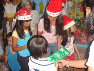 Esposa Kids Patricia, Mariegin and Regina Mae together with MCCID Registrar Ma'am Remedios Esposa assists in giving out toys and gifts.