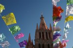 A cross on top of a Parroquia (parich church) tower and a moon seen through paper cut-out decorations for the Day of the Dead (Dia de los Muertos) in San Miguel de Allende, Mexico.
