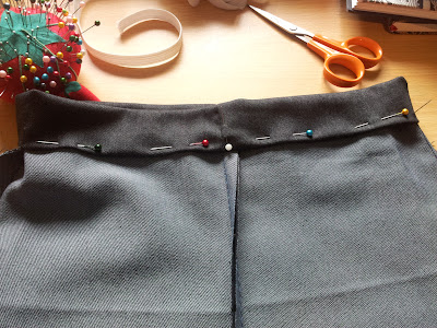 Trousers inside out again, inch-thick waistband pinned ready to sew, with white pin marking for centre front
