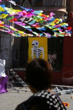 Paper cut-outs and a skeleton poster on display in front of a parish church (Parroquia) of San Miguel de Allende, Mexico on the Day of the Dead (Dia de los Muertos).
