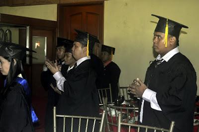 Graduates look on.