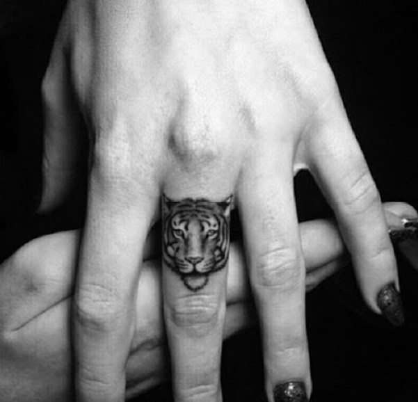 small tiger face tattoo on finger