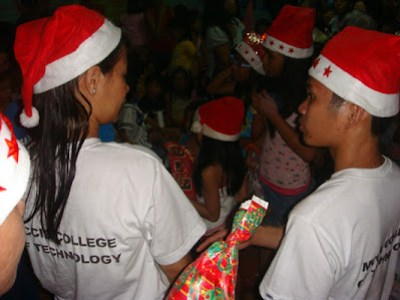 MCCID Santa Clauses' Joanna and Ariel assists in giving out gifts.