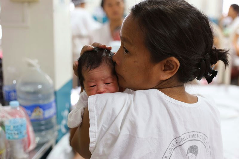 Mother carrying her baby in Fabella maternity ward