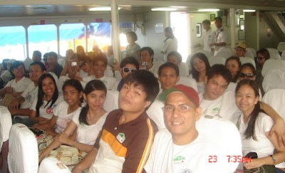 Students seated comfortably inside the ferry boat cabin.