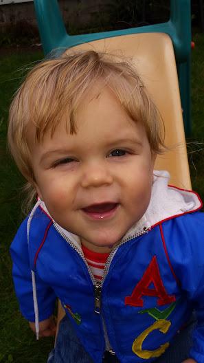 Little blonde boy in blue jacket celebrating birthday