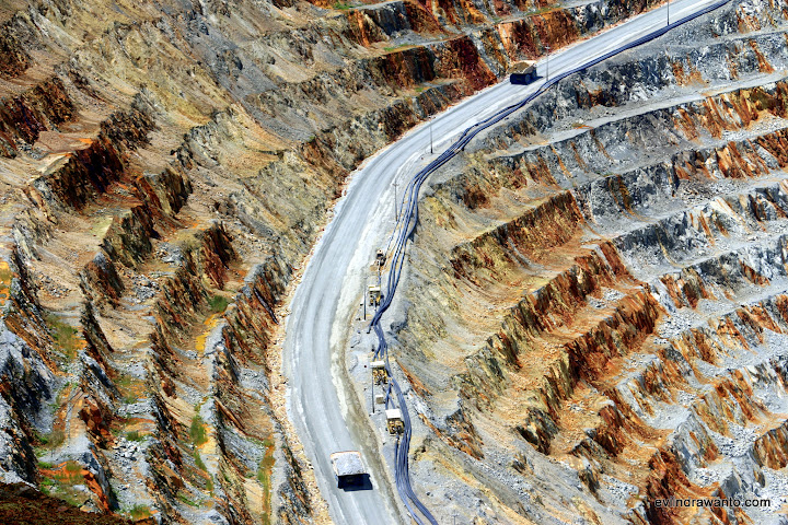 Dua buah haul truck bermuatan 240 ton batuan sedang menyisir jalan curam di sepanjang dinding pit menuju crusher