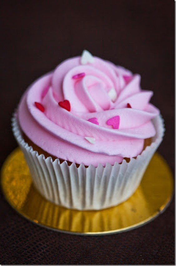 Vanilla cupcake with pink frosting and heart sprinkles.