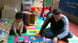 Paul playing with a kid in a child friendly space