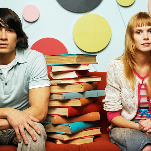 Young Couple Sitting with a Pile of Books --- Image by © Royalty-Free/Corbis
