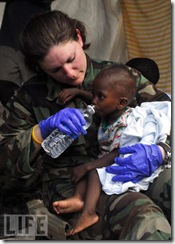 US Navy Chief Hospital Corpsman Rioni, gives water to a dehydrated child after the devastating Haiti earthquake