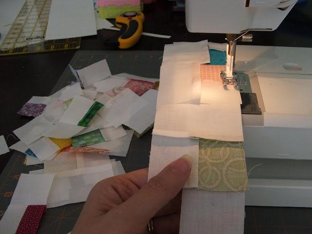 We started sewing all those squares to strips of white fabric
