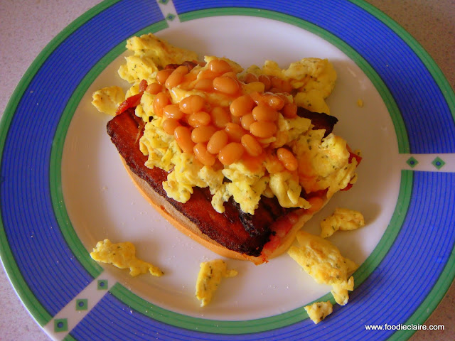 Scrambled egg on hard dough bread with plaintain, bacon and beans