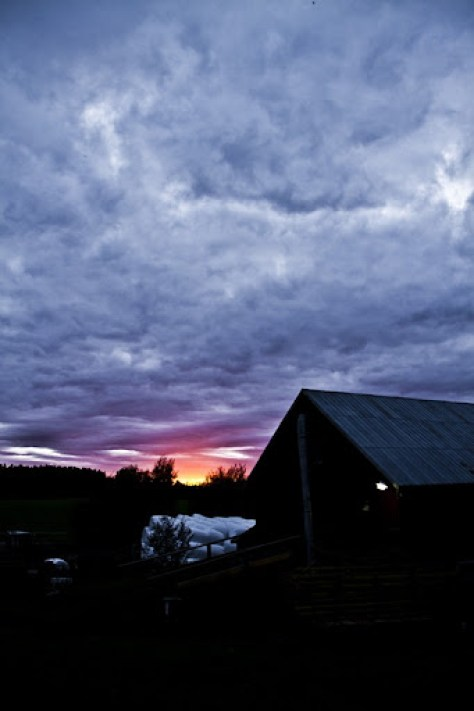 Sunset and clouds behind barn