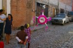 Nadia with a broom stick ready to hit her Piniata. The scene on a cobblestone street of Colonia San Rafael in San Miguel de Allende, Mexico.