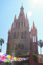 Parroquia, the parish church is a focal point of San Miguel de Allende, Mexico. In front, colorful decorations in preparations of the Day of the Dead (Dia de los Muertos).