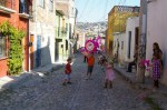 Kids getting ready to pick-up candies fallen out of the Piniata suspended over a cobblestone street of Colonia San Rafael in San Miguel de Allende, Mexico.
