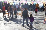 People walking in front of the parish church (Parroquia) adjacent to the main square (Jardin Allende) in San Miguel de ALlende, Mexico. The streets are decorated with paper cut-outs to celebrate the Day of the Dead (Dia de los Muertos). In the background also altars and bean paintings on the streets.