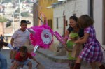 Agnieszka helping Alex hit the Piniata, which makes the kids happy to pick-up follen candy.