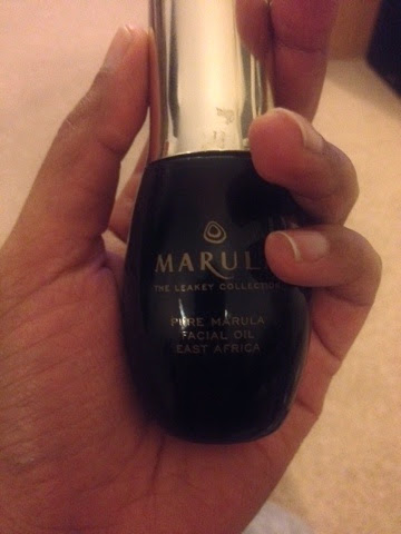 A decadent brown and gold glass bottle of Marula Oil