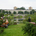 A bridge over the pond and ugly apartment buildings in the background.