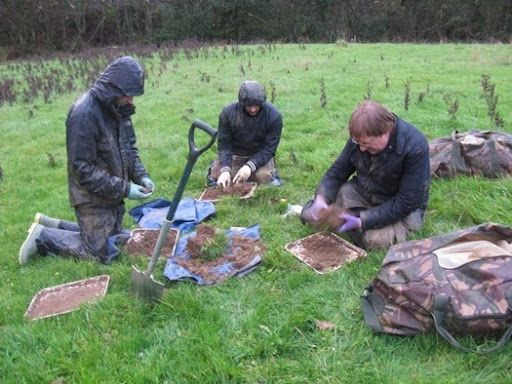 A wet and muddy Soil Biodiversity Group in the rain in Dorset