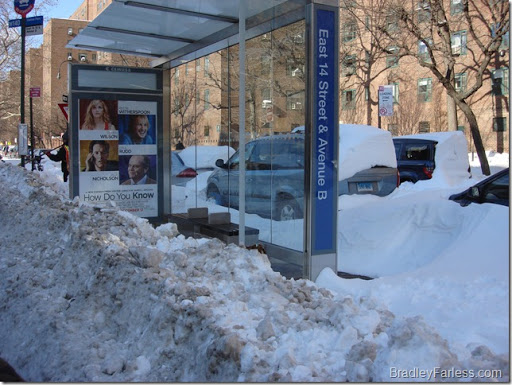 A bus stop that's blocked by snow.