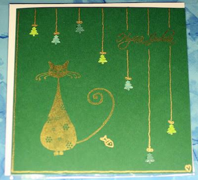 Vihreä joulukortti kultaisella kisulla ja joulukoristeilla