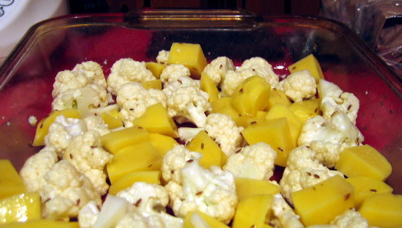 Cauliflower and potatoes before roasting in a single layer in a glass baking dish