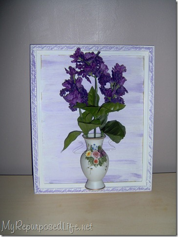 large thrift store frame holding flowers in a vintage bottle