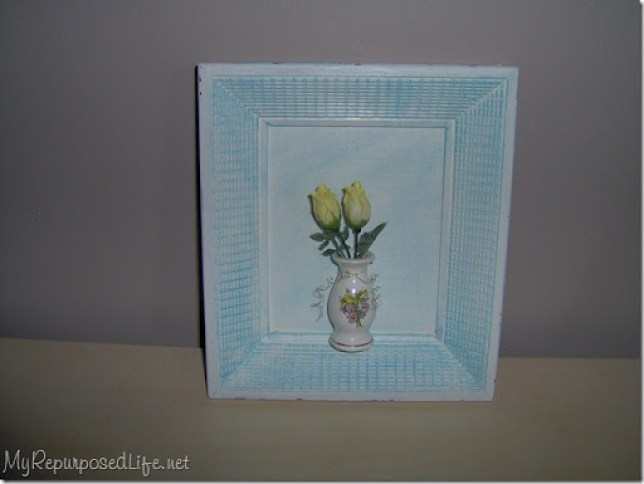 small yellow roses in a vintage bottle attached to a vintage picture frame