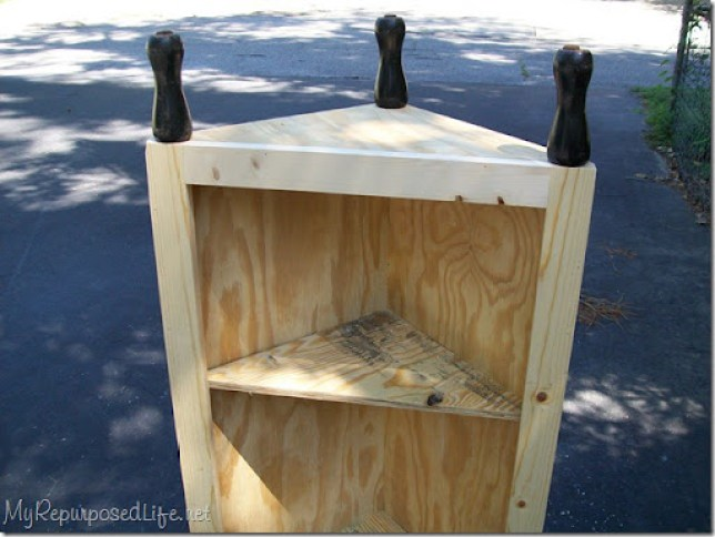 scrap spindles become legs for a diy corner cabinet
