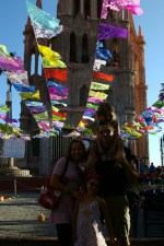 Entire family in front of the Parroquia (parish church) under paper cut-out decorations for the Day of the Dead (Dia de los Muertos) in San Miguel de Allende, Mexico.