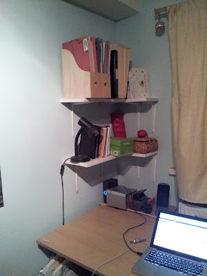 Same desk, less stuff on the desk, white shelves fixed to the walls above the back left corner of the desk