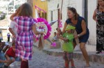Agnieszka is helping Alex hit the Piniata, other kids are picking up fallen candy.