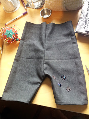 Trousers turned right-way-out, waistband still unfinished. Dark stretchy denim with beaded decoration on front left leg