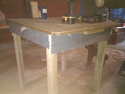 Finished wooden table standing in middle of floor