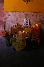 A Day of the Dead (Dia de los Muertos) altar dedicated to a local patron in a courtyard of a house near main square (Jardin Allende) in San Miguel de Allende, Mexico. A Starbucks is also located in this building.