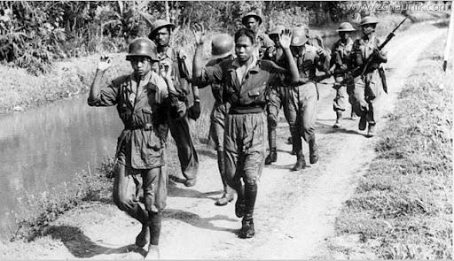 Ditangkap ekstremis Indonesia, mengangkat tangan mereka, oleh tentara Belanda (KNIL / KNIL pasukan) dikawal