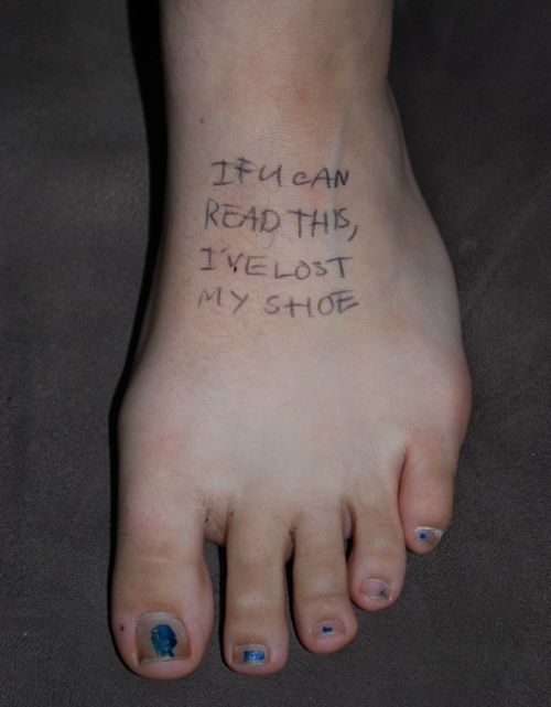 a bare foot is shown with words written on it in biro ink: IF U CAN READ THIS, I'VE LOST MY SHOE
